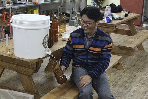 A man filling a PET bottle from a brew bucket