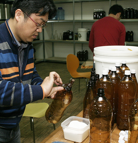 A man pours priming sugar into PET bottles